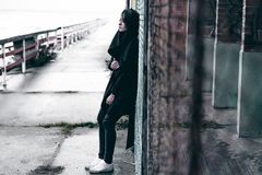 一名年轻深色的妇女的情感时兴的画象黑衣裳的,牛仔裤T恤杉,外套和太阳镜,在一个哥特式样式s 库存图片