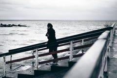 一名年轻深色的妇女的情感时兴的画象黑衣裳的,牛仔裤T恤杉,外套和太阳镜,在一个哥特式样式s 免版税图库摄影
