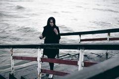 一名年轻深色的妇女的情感时兴的画象黑衣裳的,牛仔裤T恤杉,外套和太阳镜,在一个哥特式样式s 免版税库存照片