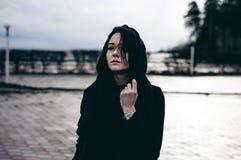 一名年轻深色的妇女的情感时兴的画象黑衣裳的,牛仔裤T恤杉,外套和太阳镜,在一个哥特式样式s 图库摄影