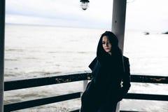 一名年轻深色的妇女的情感时兴的画象黑衣裳的,牛仔裤T恤杉,外套和太阳镜,在一个哥特式样式s 免版税库存图片