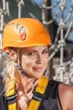 一名年轻登山人妇女的画象一件防护盔甲的反对一个绳梯的背景在冒险上升的绳索公园 库存图片