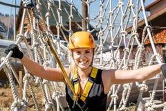 一名年轻登山人妇女的画象一件防护盔甲的反对一个绳梯的背景在冒险上升的绳索公园 免版税图库摄影