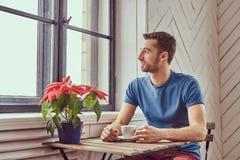 一名年轻白种人学生喝早晨咖啡在窗口 免版税库存照片