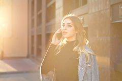 一名年轻白肤金发的妇女的情感时髦的画象一个都市风景背景特写镜头的在落日 图库摄影