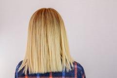 一名年轻白肤金发的妇女的背面图有突然移动理发的在浅灰色的被隔绝的背景 库存图片