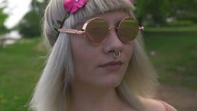 一名年轻白肤金发的嬉皮妇女和在头发佩带的镜子玻璃的洋红色桃红色花带的画象有动物之鼻圈的- 股票录像