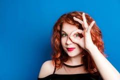 一名年轻红发妇女显示与她的手指的一个好姿态 微笑与蓝眼睛的愉快的妇女 她愉快的面孔证明 库存照片