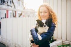 一名年轻红发白种人妇女拿着在黑白奇瓦瓦狗的两个颜色的胳膊的一条小滑稽的狗 3d明亮的重点拥抱亲吻红色翻译 库存照片