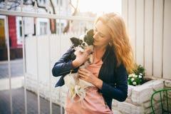 一名年轻红发白种人妇女拿着在黑白奇瓦瓦狗的两个颜色的胳膊的一条小滑稽的狗 3d明亮的重点拥抱亲吻红色翻译 库存图片