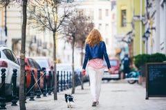 一名年轻红发白种人妇女沿有两个颜色一条小奇瓦瓦狗品种狗的欧洲街道走在一条皮带的关于 库存图片
