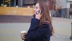 一名年轻美丽的女商人学生的画象衣服的,玻璃,走在城市附近,饮用的咖啡 股票视频