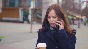 一名年轻美丽的女商人学生的画象衣服的,玻璃,走在城市附近,饮用的咖啡 影视素材