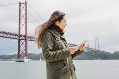 一名年轻美丽的妇女使用一种片剂与朋友沟通或看地图或其他 桥梁4月25日 免版税库存图片