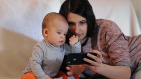 一名年轻美丽的妇女和一个小孩子仔细地看智能手机慢动作射击的屏幕 股票录像