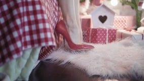 一名年轻美丽的妇女在红色高跟鞋走在圣诞树附近,下来坐床并且离开 股票录像