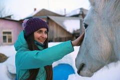 一名年轻美丽的妇女抚摸马并且微笑 免版税库存图片