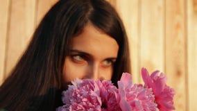 一名年轻美丽的妇女的画象的慢动作有牡丹花束的  影视素材