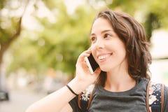 一名年轻美丽的妇女的画象谈话与她的智能手机 库存照片