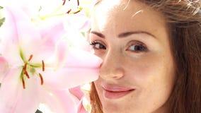 一名年轻美丽的妇女的面孔有百合特写镜头的 女孩享用并且嗅到花气味  温泉 Aromateripia 股票录像