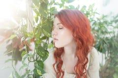 一名年轻美丽的梦想的红头发人妇女的嫩画象在叶子中的 免版税库存图片
