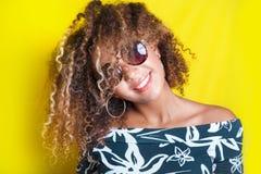 一名年轻美国黑人的妇女的画象太阳镜的 黄色背景 生活方式 免版税图库摄影