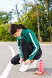 一名年轻运动的妇女阻塞在运动鞋的鞋带 有做锻炼的完善的身体的一个女孩 免版税库存照片