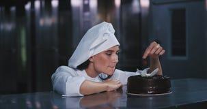 一名年轻迷人的妇女在蛋糕上把樱桃放小心地在欢欣和慢慢地与照相机衔接 股票录像