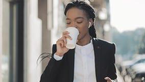 一名年轻非裔美国人的女实业家的画象衣服的,走在城市,饮用的咖啡和使用附近 股票录像