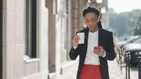 一名年轻非裔美国人的女实业家的画象衣服的,走在城市,饮用的咖啡和使用附近 股票视频