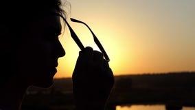 一名年轻魅力妇女投入太阳镜用她的手在日落在slo mo 股票录像