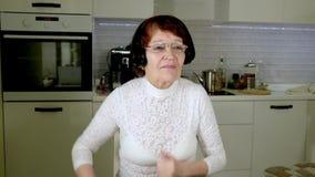 一名年长妇女听到在耳机的音乐从电话,姿势示意精力充沛地并且跳舞 股票视频