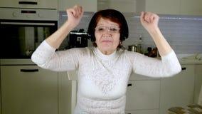 一名年长妇女听到在耳机的音乐从电话,姿势示意精力充沛地并且跳舞 影视素材