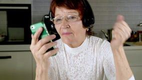 一名年长妇女听到在耳机的音乐从电话,姿势示意精力充沛地并且跳舞 股票录像