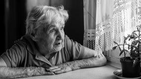 一名年长妇女哀伤地看窗口 寂寞 免版税库存图片