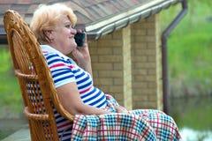 一名年长妇女在一把柳条摇椅和谈话坐手机 好通信 在乡间别墅里放松 免版税库存照片