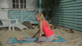 一名年长妇女在房子附近舒展她的在沙子的腿 股票录像