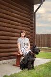 一名年长妇女坐与一只黑髯狗的一条村庄长凳在一个木房子附近在乡下 免版税图库摄影