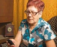 一名年长妇女拜访移动电话。 免版税库存图片