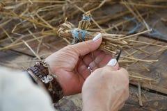 一名年长妇女的手做秸杆玩具 r 图库摄影