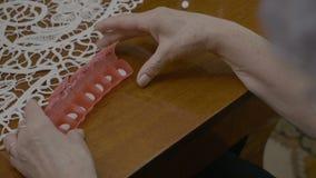 一名年长妇女的手她的疗程为下星期做准备使用一位每日药片计划者在客厅- 股票录像