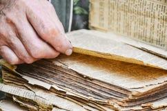 一名年长妇女读圣经 一个年长人的手通过一本老古色古香的书的页翻转 r的概念 库存图片