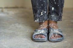 一名建筑工人的脚老肮脏的衣裳和鞋子的 库存照片