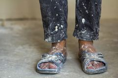 一名建筑工人的脚老肮脏的衣裳和鞋子的 免版税库存照片