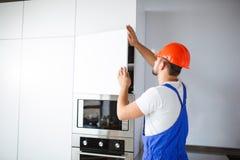 一名建筑工人,制服的,设定了厨房家具 库存照片