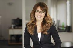 一名微笑的专业成熟女实业家的画象 免版税库存照片