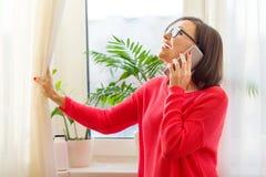 一名微笑的中年妇女在电话谈话,打开帷幕并且看晴朗的窗口 侧视图 免版税库存照片