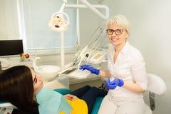 一名微笑的妇女的画象,坐在与医生的牙齿椅子在牙齿办公室 免版税库存照片