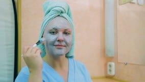 一名微笑的妇女的面孔有一块毛巾的在她的有蓝色黏土刷子的头在她的皮肤的 平均计划 股票录像