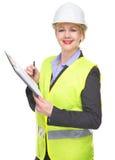 一名微笑的妇女的画象安全背心和安全帽文字的在剪贴板 免版税库存图片